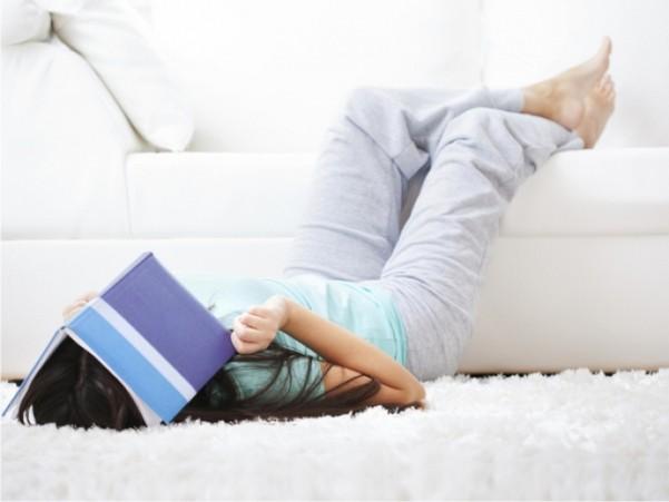 девушка накрыла книгой лицо