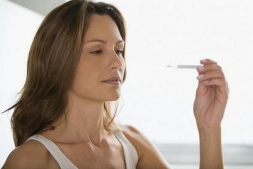 женщина измеряет температуру